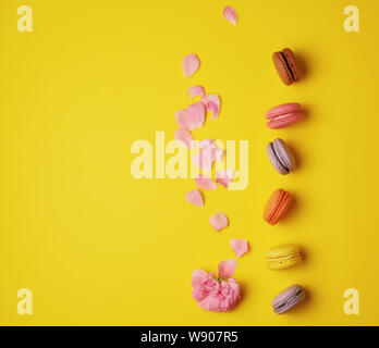 sweet multi-colored macarons with cream and a pink rose bud with scattered petals on a yellow  background, top view, flat lay, copy space - Stock Photo