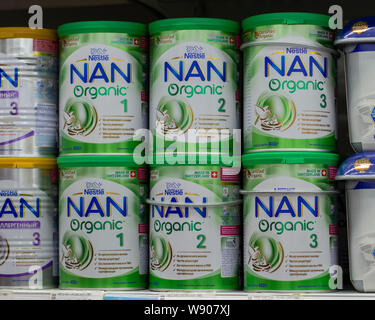 03-08-2019 Moscow, Russia. Baby food milk formula organic NAN Nestle in large white green metal cans on a store shelf. Dry mix for feeding young child - Stock Photo