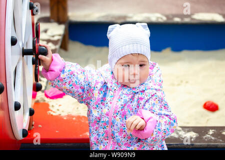 Girl 1 year walks on the playground, playing with children's sports equipment. Baby jacket with flowers and a gray knitted hat for a walk. independent - Stock Photo