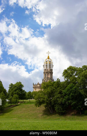 Stone temple with a high belfry, one golden dome and a golden Christian cross on top. Beautiful majestic orthodox Christian church in the estate of Du - Stock Photo