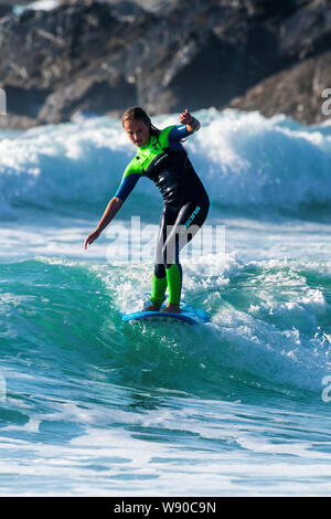 A female surfer riding a wave at Fistral in Newquay in Cornwall. - Stock Photo