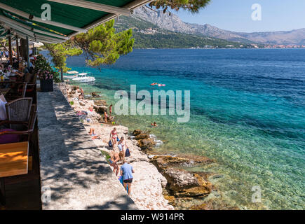 Restaurants on the walls of Korcula old town and the beach under the walls - Stock Photo
