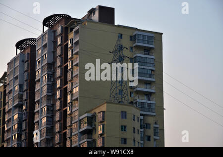 A pylon stands on the rooftop of a residential apartment building in Dazhou city, southwest Chinas Sichuan province, 17 April 2013.   A pylon mounted - Stock Photo