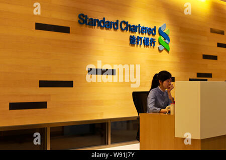 --FILE--A Chinese employee works at a branch of London-listed Standard Chartered Bank in Shanghai, China, 14 November 2011.   Standard Chartered notch - Stock Photo