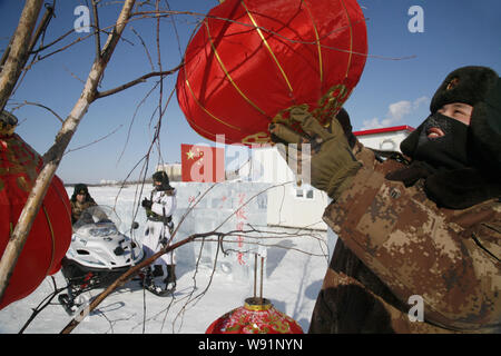 A Chinese PLA (Peoples Liberation Army) soldier hangs up red lanterns on a tree in the snow to celebrate the Chinese Lunar New Year, also known as the - Stock Photo
