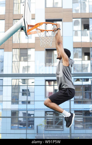 Side view action shot of African basketball player jumping to hoop while training in outdoor court, copy space