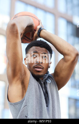 Action portrait of African basketball player shooting ball while practicing in outdoor court