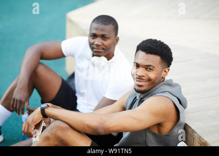 High angle portrait of two African-American guys smiling at camera while chilling in skate park outdoors, copy space - Stock Photo