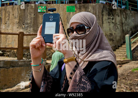 WOMAN WEARING A NIQAB VEIL AND A SMARTPHONE IN SRI LANKA - Stock Photo