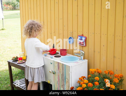 Girl play outdoors in so called mud kitchen, where you can make fake food, play with sand, dirt, water, plants and make a mess. - Stock Photo