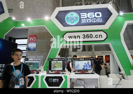 --FILE--A Chinese employee walks past the stand of wan 360.cn of Qihoo during the 11th China Digital Entertainment Expo and Conference, known as China - Stock Photo