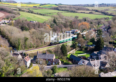 Corfe Castle, England, UK - March 27, 2019: A steam train pulls away from Corfe Castle station on the Swanage Railway heritage line in Dorset's Purbec - Stock Photo