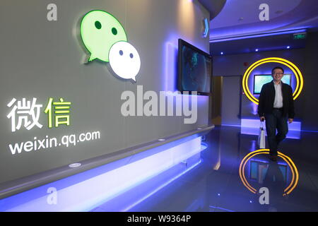 --FILE--A Chinese employee walks past a logo of Weixin.com (Wechat) at the headquarter of Tencent in Shenzhen, southeast Chinas Guangdong province, 28 - Stock Photo