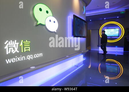 --FILE--A Chinese employee walks past a signage of mobile messaging app Weixin, or WeChat of Tencent at the headquarters of Tencent in Shenzhen, south - Stock Photo