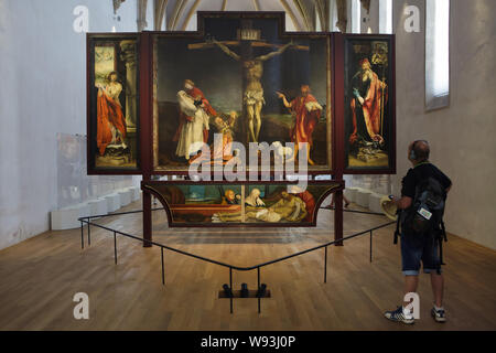 Visitor in front of the Isenheim Altarpiece by German Renaissance painter Matthias Grunewald (1512–1516) displayed in the Unterlinden Museum (Musée Unterlinden) in Colmar, Alsace, France. First view of the Isenheim Altarpiece with Crucifixion framed by the martyrdom of Saint Sebastian on the left, and by Saint Anthony the Great on the right is seen in the picture. - Stock Photo