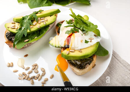 Breakfast. Bread toasts with poached egg and avocado with spinach, fresh arugula and seeds - Stock Photo
