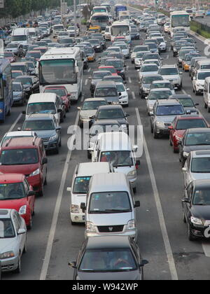Masses of vehicles move slowly on a road during a traffic jam in Beijing, China, 2 September 2013.   Beijings traffic authorities will use motorbikes - Stock Photo
