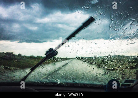 drivers view of heavy rain through car window - Stock Photo