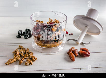 ingredients for energy balls in a blender on white background with copy space - Stock Photo