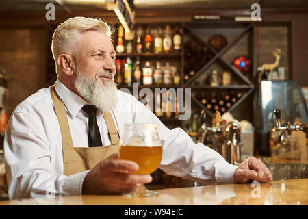 Side view of bearded man wearing white shirt and apron looking forward while keeping glass of light beer in hand. Male brewer standing over bar and smiling. Concept of beverage and drinking. - Stock Photo