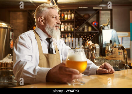View from side of nice man wearing white shirt and apron standing over bar and drinking light beer. Professional male brewer looking forward and keeping glass of alcohol. Concept of beverage. - Stock Photo
