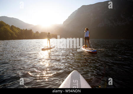 Mother and son paddling on sup on the emerald colored spring waters of alpine Lake Bohinj, Slovenia at sunset