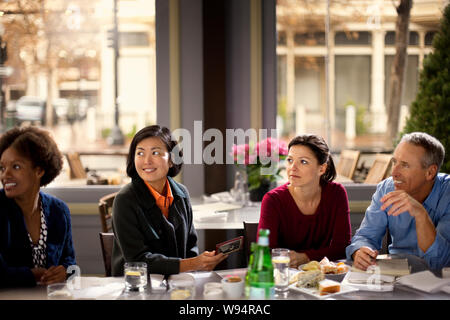 Smiling group of colleagues enjoy a lunch meeting together. - Stock Photo