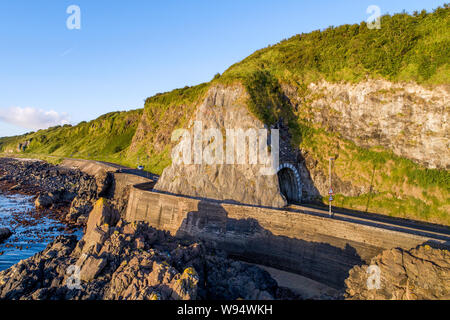 Black Arc tunnel  and Causeway Coastal Route. Scenic road along eastern coast of County Antrim, Northern Ireland, UK. Aerial view in sunrise light - Stock Photo