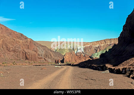 Road in colorful mineral mountains, part of the landscapes of Rainbow Valley also known as Valle de Arco Iris in the Atacama Desert of Chile