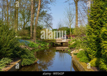 view of small canal, people sit on small bridge and garden with bush, shrub, tulips flower and trees in spring season at Keukenhof gardens. - Stock Photo