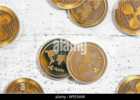 Top down view, XRP ripple cryptocurrency golden coins on white stone like board - Stock Photo