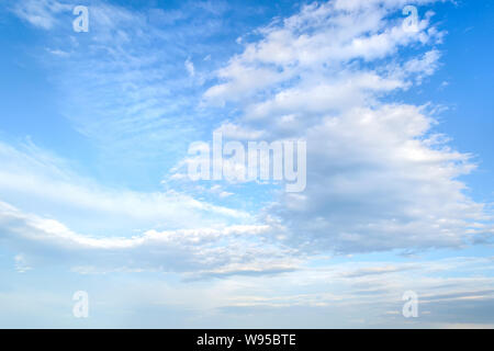 White light fluffy stratus and cirrus clouds high in the blue summer sky. Different cloud types and atmospheric phenomena. Skyscape on a sunny day. - Stock Photo
