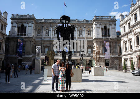 People outside the entrance to the Royal Academy for the Summer Show in London, United Kingdom. The Summer Exhibition is an open art exhibition held annually by the Royal Academy in Burlington House, Piccadilly in central London, England, during the months of June, July, and August. The exhibition includes paintings, prints, drawings, sculpture, architectural designs and models, and is the largest and most popular open exhibition in the UK. It is also the longest continuously staged exibition of contemporary art in the world. - Stock Photo