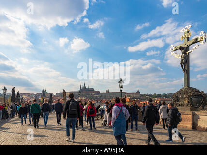 Outdoor sunny view of crowd of tourists  and  Statuary of holy Crucifix and Calvary on Charles Bridge,and background of Castle and St. Vitus Cathedral - Stock Photo