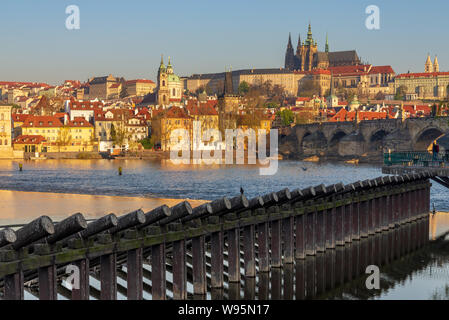 Outdoor sunny view of Charles Bridge, Prague Castle, St. Vitus Cathedral,  buildings on riverside, and wooden piles barrier stand on Vltava River. - Stock Photo