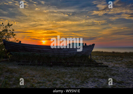Old fisher boat in Baltic sea during sunset - Stock Photo