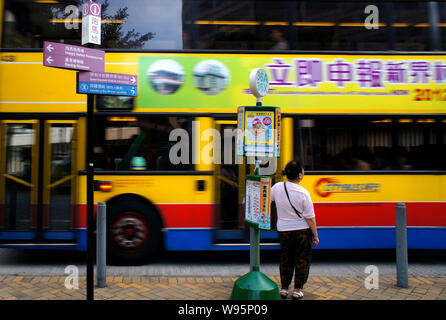 A passenger waits at a bus station while a double-decker bus passes by in Happy Valley, Hong Kong, China, 27 June 2012.   Chinas State Council, or the - Stock Photo