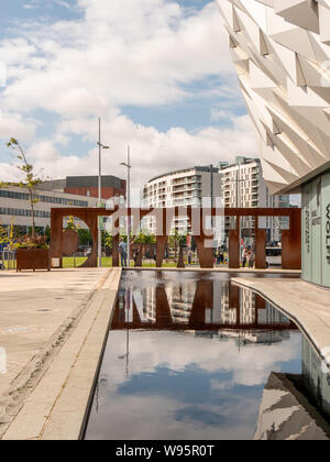 Metal Titanic sign at Titanic Belfast building with reflection in water - Stock Photo
