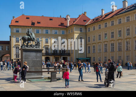 Crowd of people and tourists enjoy sunny day and take a picture at the square in front of Great South Tower of the Saint Vitus Cathedral. - Stock Photo