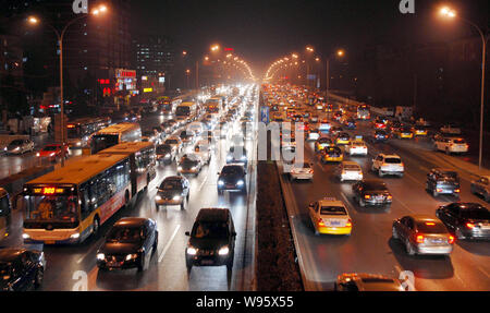 --FILE--Night view of masses of cars and buses moving slowly during a traffic jam in Beijing, China, 16 January 2012.   The number of cars registered - Stock Photo