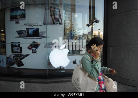 --File--A woman walks past an Apple Store in Beijing, China, 24 October 2011.    Apple Inc is embracing Chinese developers in a bid to increase its ma - Stock Photo