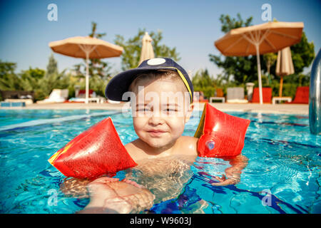 a little boy learns to swim in the pool in the summer with the support of his father's hands - Stock Photo