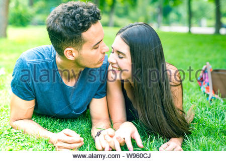 Young Couple in Love Smiling and Kissing in Central Park Lying Down - Stock Photo