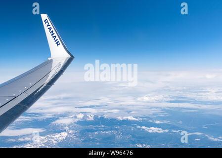 Austria - 07 July, 2019: Flight Palma de Mallorca, Spain - Krakow, Poland. Ryanair airplane wing on sky background. Above the Alps mountains. - Stock Photo