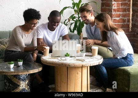 Happy diverse friends have fun watching funny video in caf - Stock Photo
