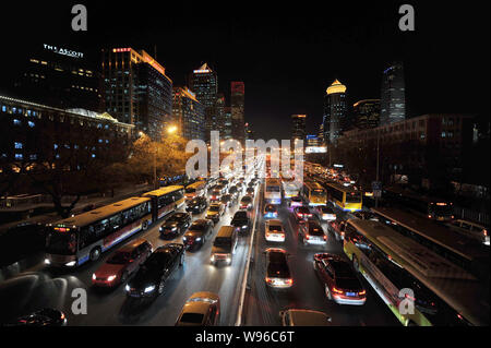 --FILE--Night view of masses of cars and buses moving slowly during a traffic jam in Beijing, China, 23 December 2011.   The number of cars registered - Stock Photo