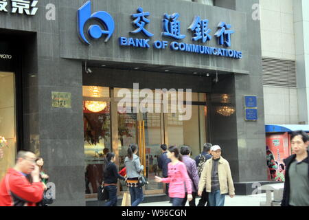 --File--Pedestrians walk past a branch of Bank of Communications (BoCom) in Chongqing, China, 28 March 2012.   Bank of Communications Corp., the count - Stock Photo