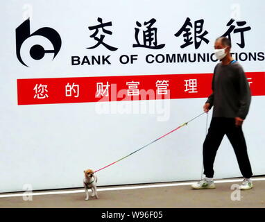 --File--A pedestrian walks his dog past an advertisement for Bank of Communications (BoCom) in Shanghai, China, 9 September 2011.   Bank of Communicat - Stock Photo