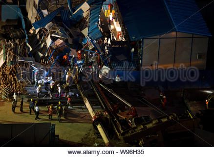 Rescuers are seen at the accident site where a pile driver toppled over and destroyed a shed in Shenzhen, south Chinas Guangdong province, 14 April 20 - Stock Photo
