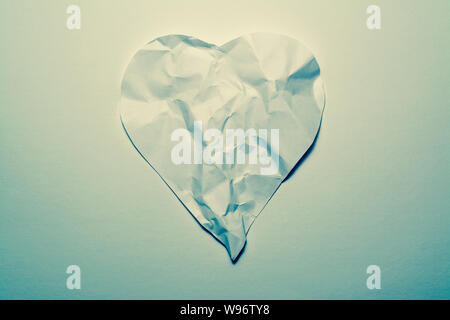 Heart symbol made from old, crumpled paper on a white vintage background. Symbol of a broken heart, unhappy love. - Stock Photo